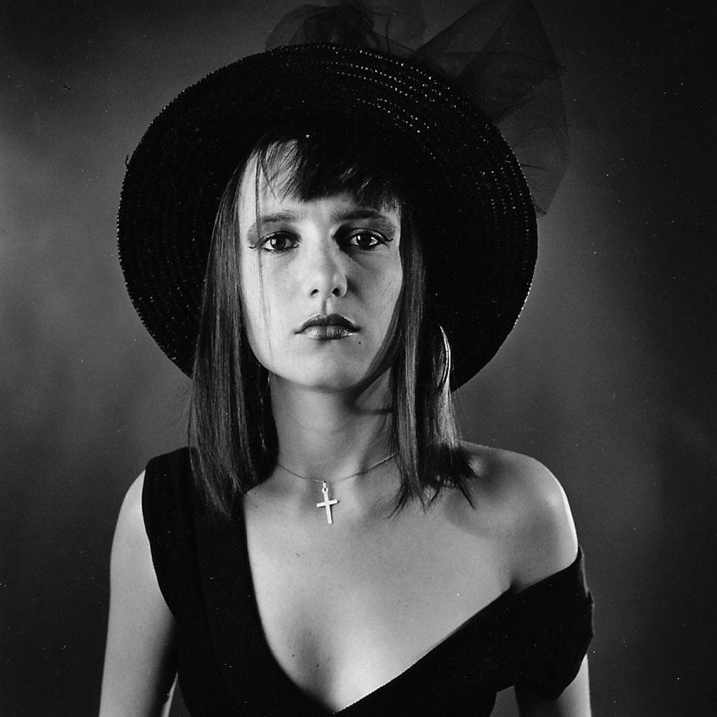 Portrait photographique noir blanc d'une jeune fille au chapeau par Christian Rossier