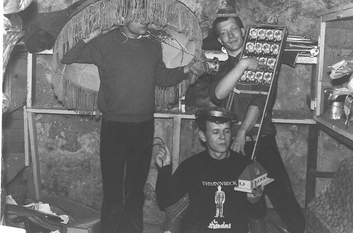 Photographie noir blanc ed trois jeunes, avec un abat-jour sur la tête