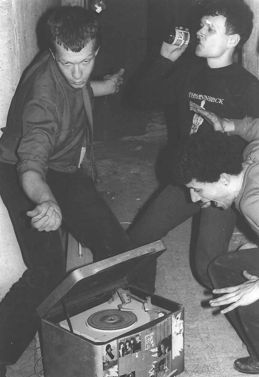 Photographie noir blanc d'un groupe de jeunes hommes avec un tourne-disque